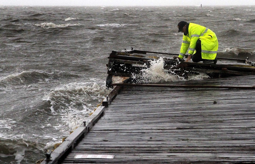 Начальник полиции Виргил Сэндлин (Virgil Sandlin) на коленях пытается обезопасить небольшой плавучий док от сильного тропического шторма «Дебби», Сидар-Ки, Флорида, США. Сэндлин говорит, что это было похоже на езду на диком мустанге в попытках сохранить равновесие.