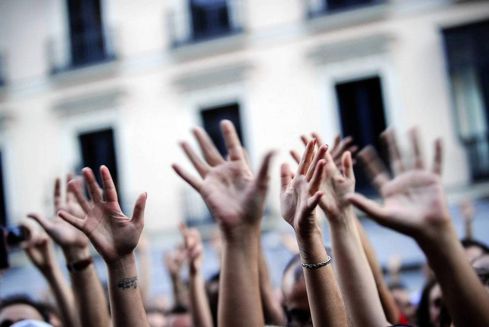 Демонстранты Бро поднимают руки вверх во время митинга в Мадриде, Испания. Испанцы протестуют против финансового кризиса в стране, который, по их мнению, возник из-за недобросовестных банков и коррумпированных политиков.