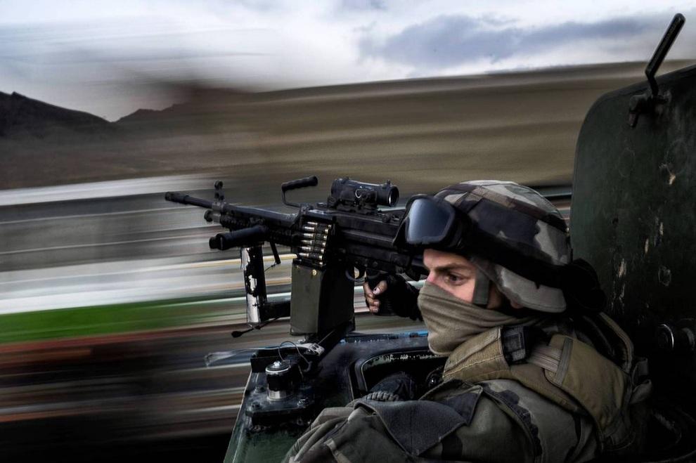Французский солдат Бро сидит за пулеметом во время патрулирования дороги между базой в Неджрабе и складской базой у Кабула, Афганистан.