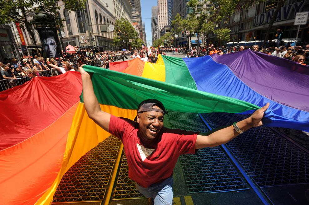 Марк Вилсон (Mark Wilson) несет радужный флаг во время 42-го ежегодного гей-парада в Сан-Франциско, штат Калифорния, США, 24 июня 2012 года.