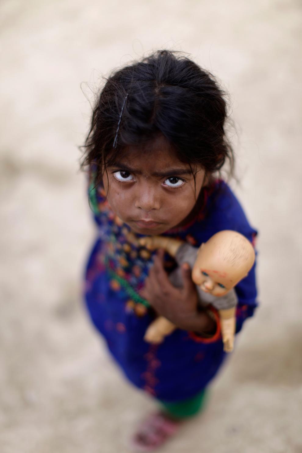 5-летняя Сайма Хашим (Saima Hashim) смотрит на фотографа в трущобах на окраине Исламабада, Пакистан, 18 июня 2012 года. Ее семья была вынуждена покинуть свою деревню в провинции Синд в Пакистане во время наводнения в 2010 году.
