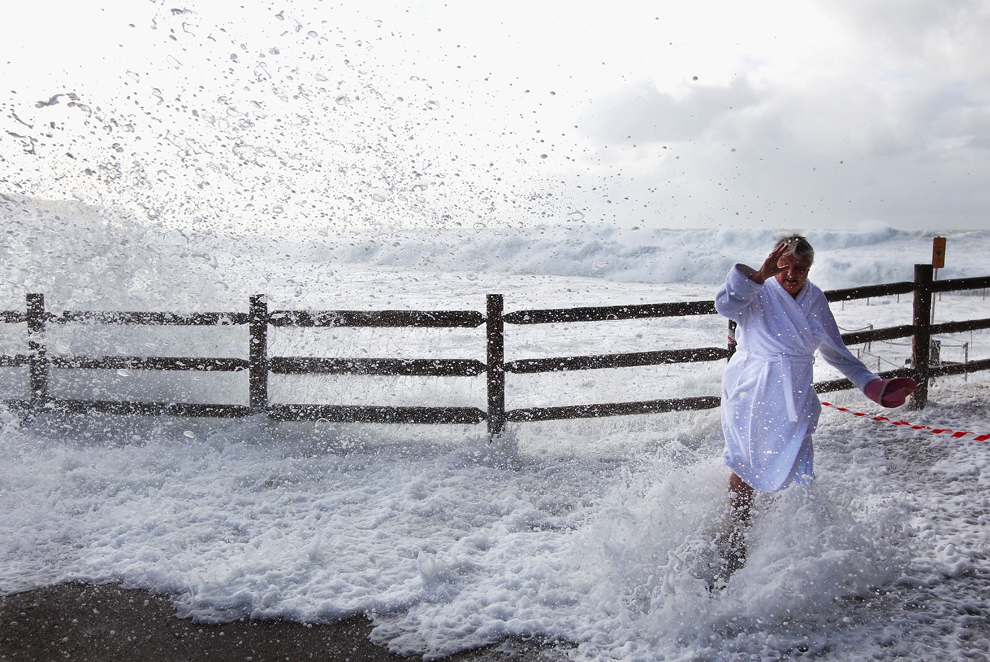 Женщина прикрывает лицо от брызг волн на пляже Бронте, Сидней, Австралия, 6 июня 2012 года.