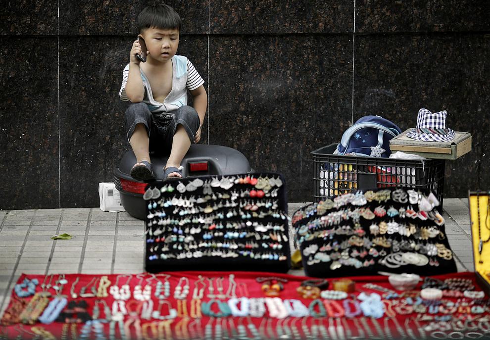 Мальчик разговаривает по мобильному телефону, наблюдая за лотком с бижутерией в Шанхае, Китай, 11 июня 2012 года.