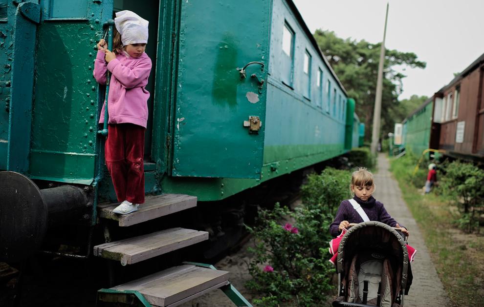 Дети играют возле старых вагонов в городке Хель на побережье Балтийского моря к северу от Гданьска, Польша, 24 июня 2012 года. В этих вагонах живут несколько бедных семей.