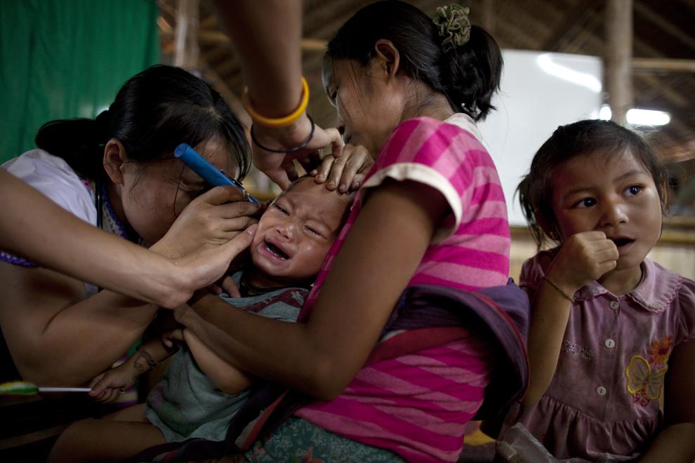 Бирманский врач осматривает ребенка в лагере для беженцев Мэй-Ла в провинции Так, Таиланд, 6 июня 2012 года.