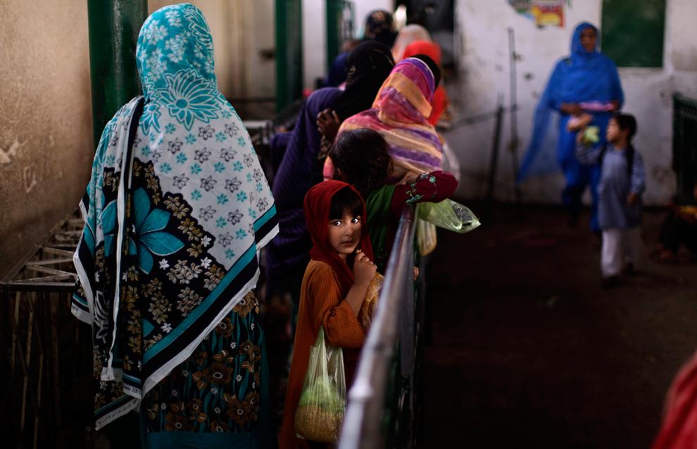 Пакистанская девочка стоит в очереди с другими женщинами и детьми, чтобы получить порцию риса в суфийском храме Бери Имама, Исламабад, Пакистан, 8 июня 2012 года.