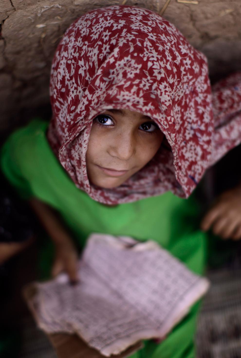 5-летняя Лайла Хазрат (Layla Hazrat) читает Коран во время урока в школе в местной мечети на окраине Исламабада, Пакистан, 7 июня 2012 года.