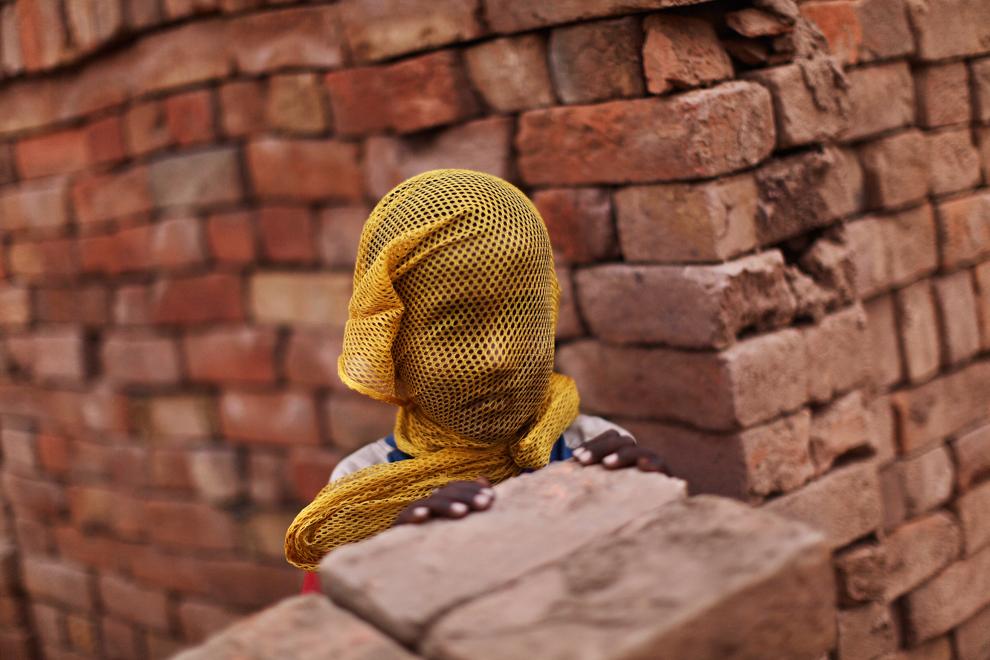 Мальчик, который живет около кирпичного завода, защищает лицо сеткой во время песчаной бури на окраине Исламабада, Пакистан, 6 июня 2012 года.