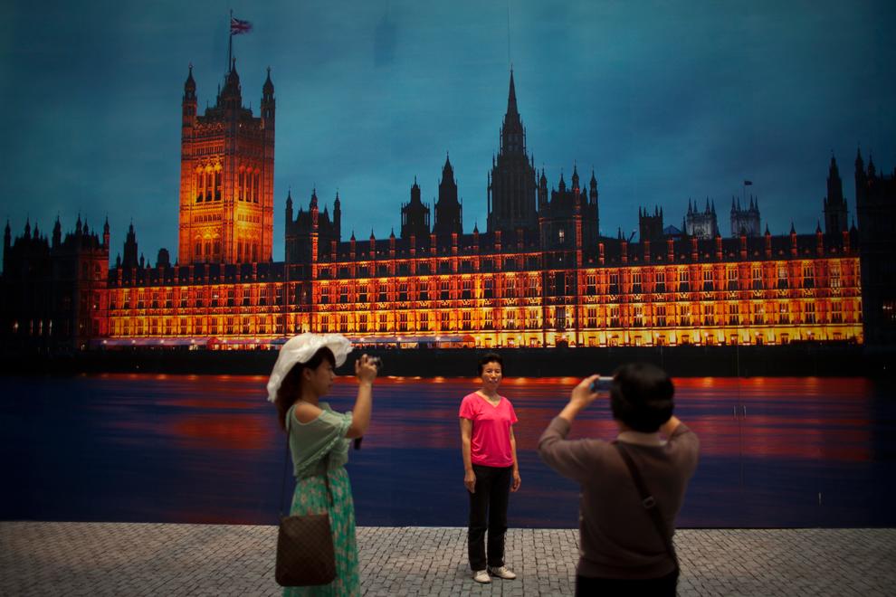Туристы фотографируются на фоне панорамной фотографии Вестминстерского дворца в пекинском национальном плавательном комплексе (Водяной куб), Пекин, Китай, 7 июня 2012 года.