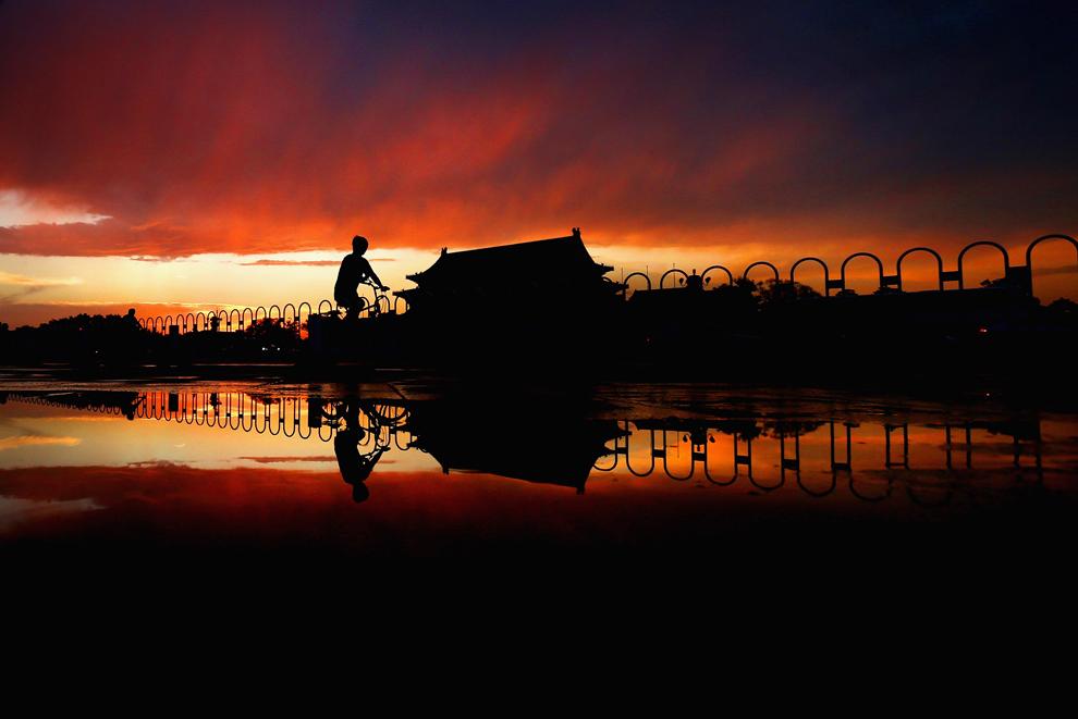 Мужчина едет на велосипеде по площади Тяньаньмэнь перед традиционной церемонией спуска флага в Пекине, Китай, 9 июня 2012 года.