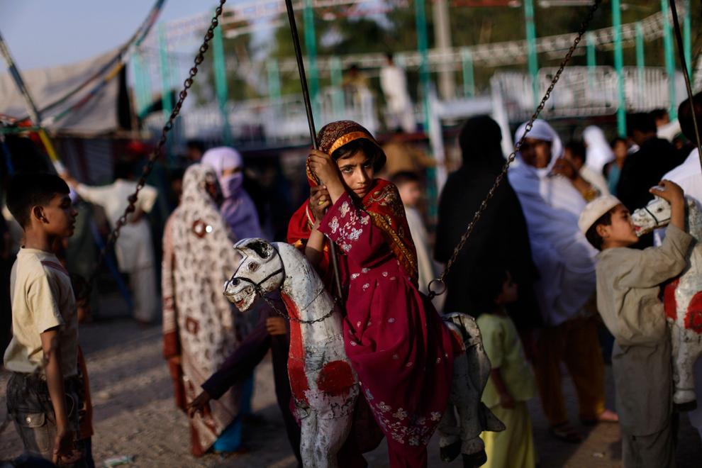 Пакистанская девочка сидит на карусели, надеясь покататься бесплатно в парке развлечений в Равалпинди, Пакистан, 13 июня 2012 года.