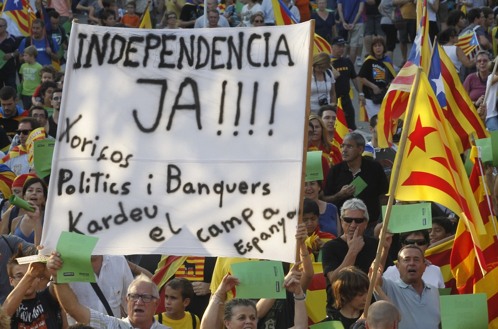 Marchers hold a banner and Catalonian nationalist flags as they demonstrate during Catalan National Day in Barcelona