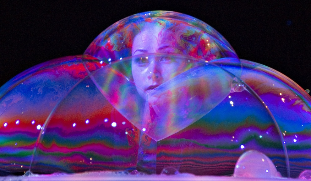 Bubble artist Melody Yang looks through bubbles she created on a table during a demonstration in Vancouver