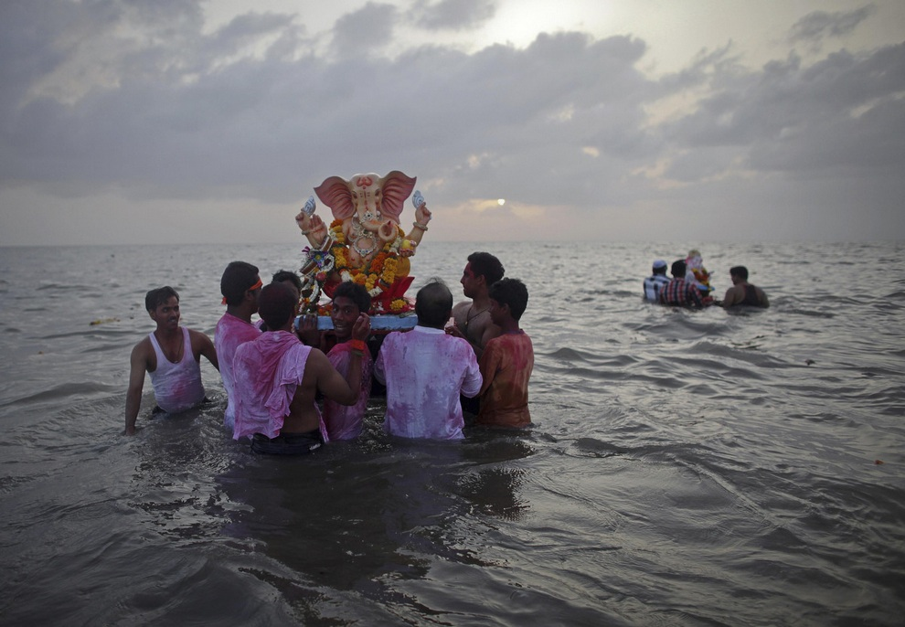 Верующие несут статую индуистского божества Ганеши в воды Аравийского моря, Мумбаи, Индия, на первый из десяти дней фестиваля «Ганеша-Чатуртхи».