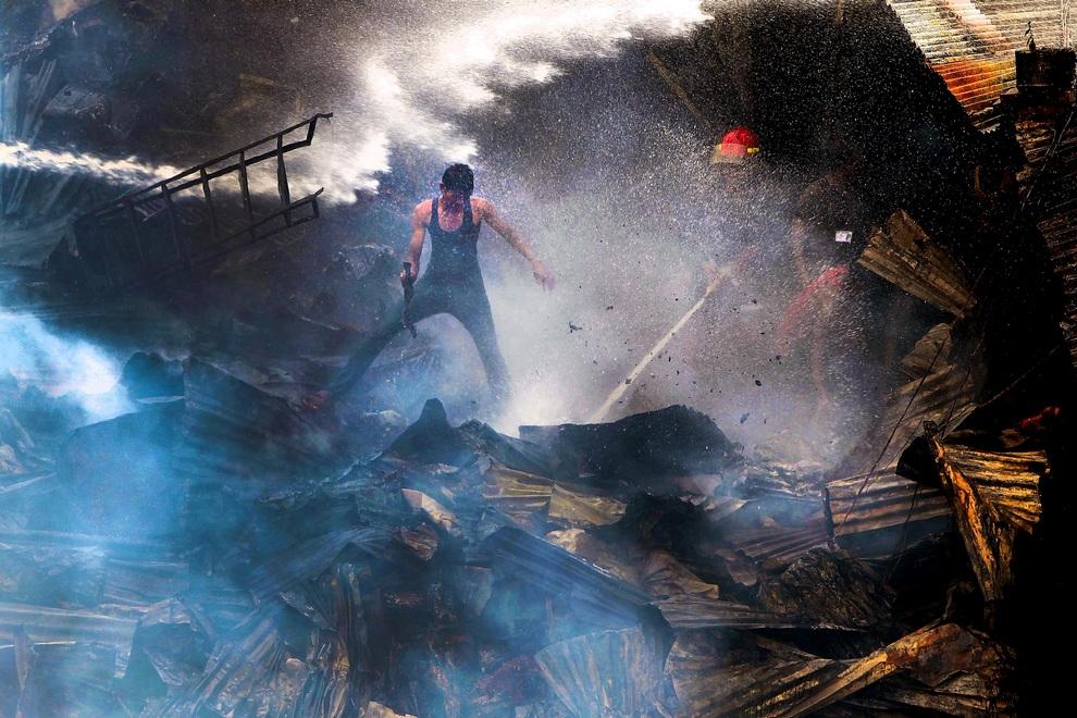 Пожарные и местные жители пытаются взять под контроль огонь в трущобах Дакки, Бангладеш. Возгорание привело к уничтожению не менее 500 лачуг.