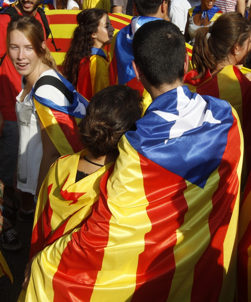 A couple wrapped in a Catalonian nationalist flag take part in a demonstration during Catalan National Day in Barcelona