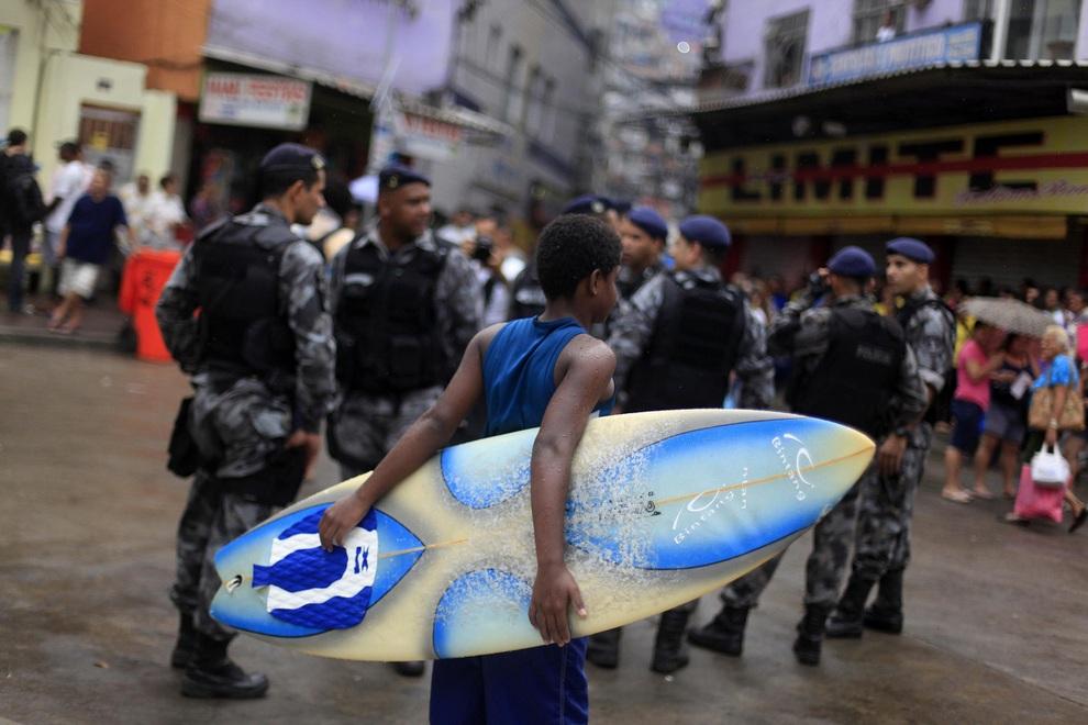 Мальчик с доской для серфа смотрит на полицейских, Росинья, Рио-де-Жанейро, Бразилия. Одной из самых сложных задач Бразилии перед чемпионатом мира по футболу 2014 года является зачистка крупных криминальных районов.