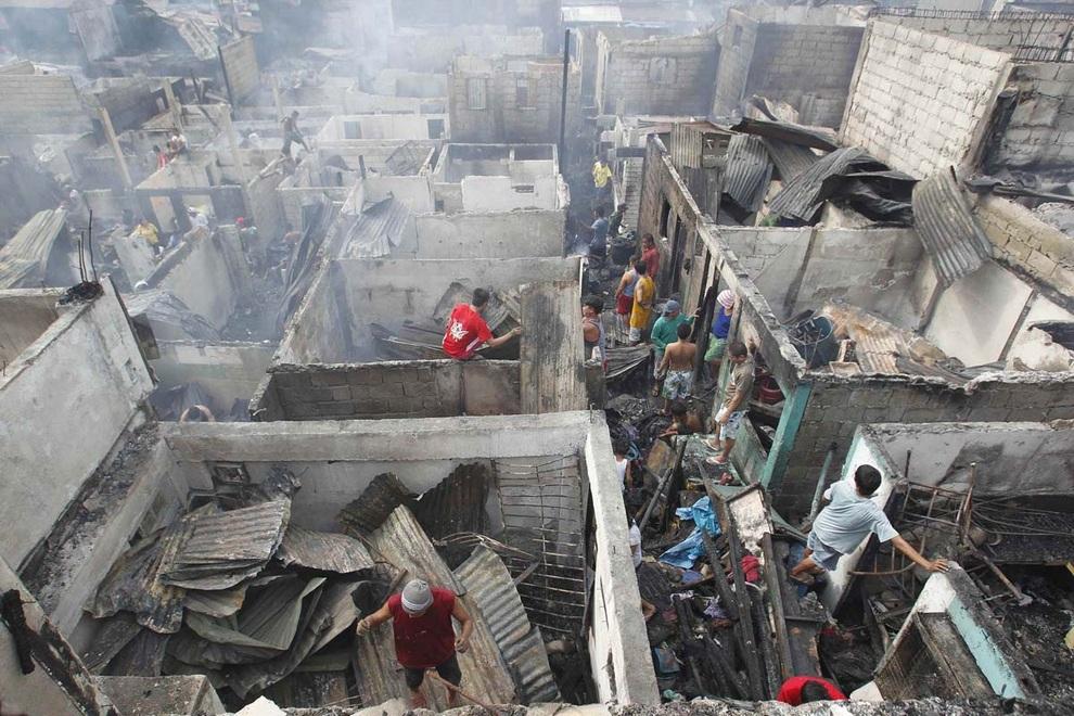 Люди пытаются спасти свои вещи после сильного пожара, охватившего свыше 200 домов в Кесон-Сити, Манила, Филлипины. Один чеговек погиб, 800 семей осталось без жилья.