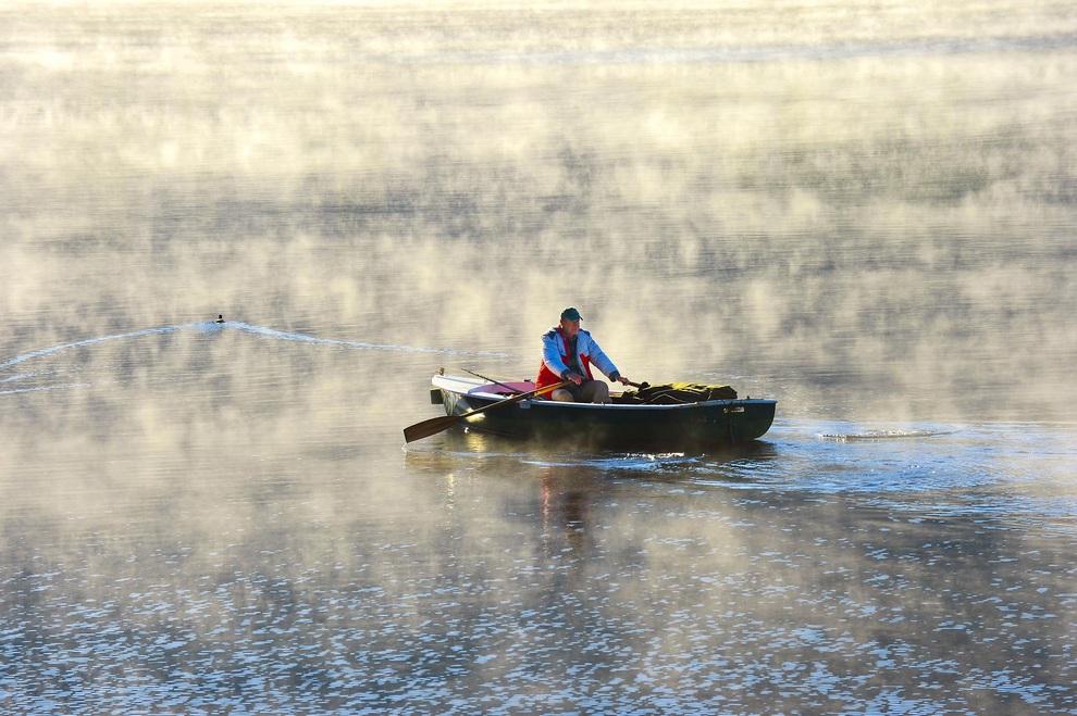 Рыбак плывет на лодке сквозь пелену утреннего тумана на озере Титизее в Шварцвальде, Германия.