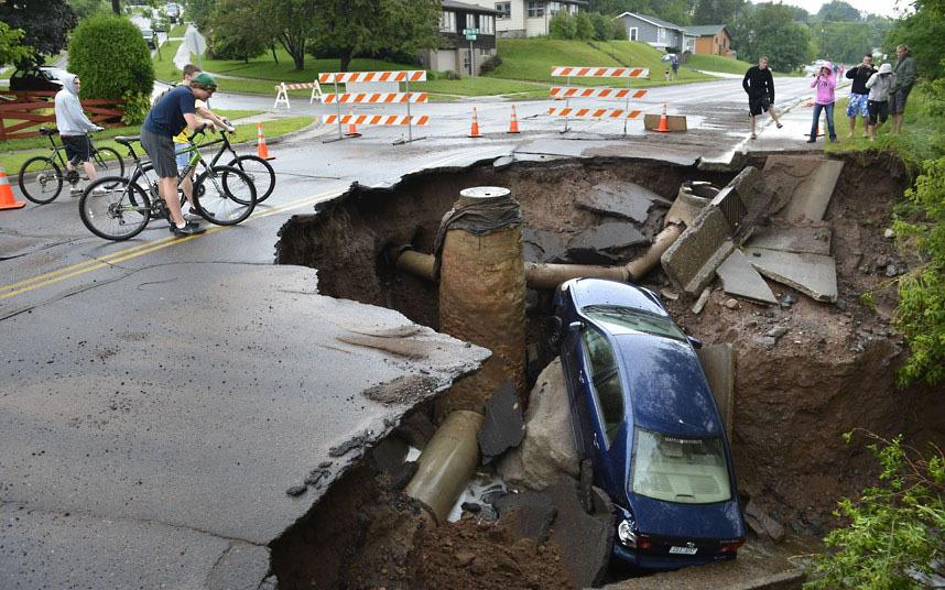 Июнь 2012г., автомобиль в воронке в Дулуте, Миннесота, после того, как наводнением размыло дороги.