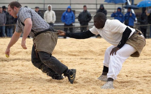 Senegalese wrestler Pouye holds an opponent during a fight at a qualification tournament in Romont