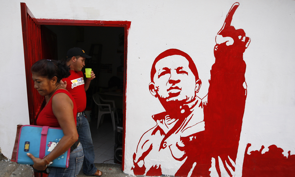 A woman leaves a campaign office of United Socialist Party of Venezuela (PSUV) with a painting of President Hugo Chavez in the neighborhood of Petare in Caracas November 12, 2008. Venezuelans go to the polls on Nov. 23 to elect state governors and city mayors.  REUTERS/Jorge Silva (VENEZUELA)